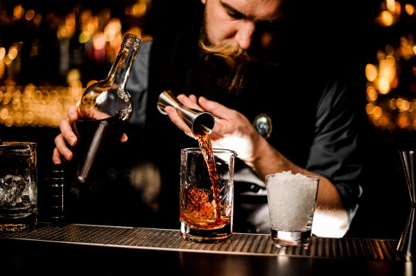 Bartender pouring a brown alcohol to the cocktail from the steel jigger to a glass on the bar counter on the blurred background